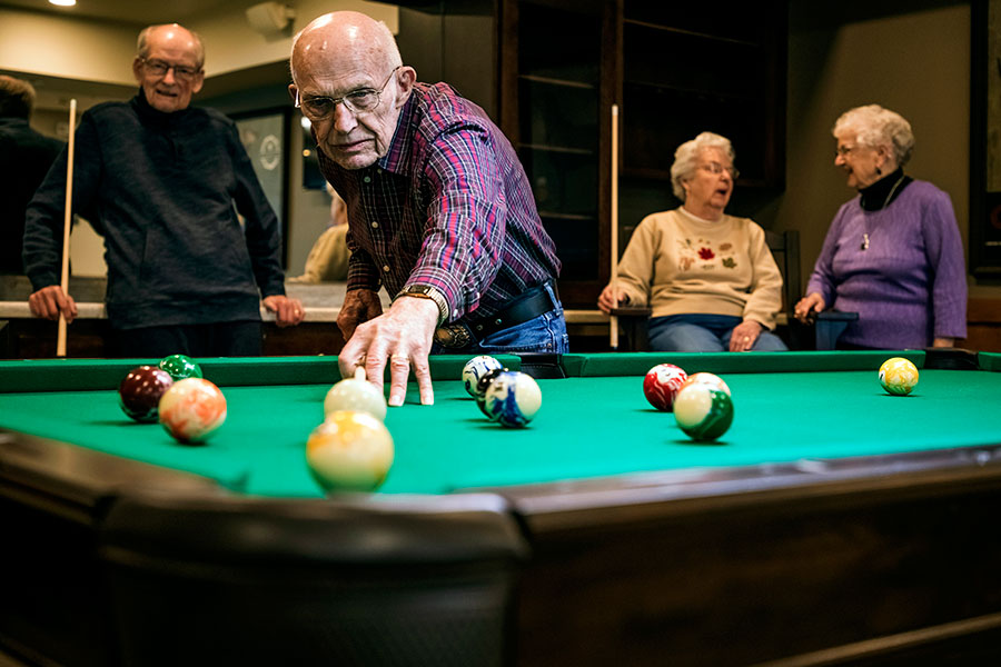 Residents playing pool in pub room at Peaceful Pines Senior Living Community Rapid City, South Dakota